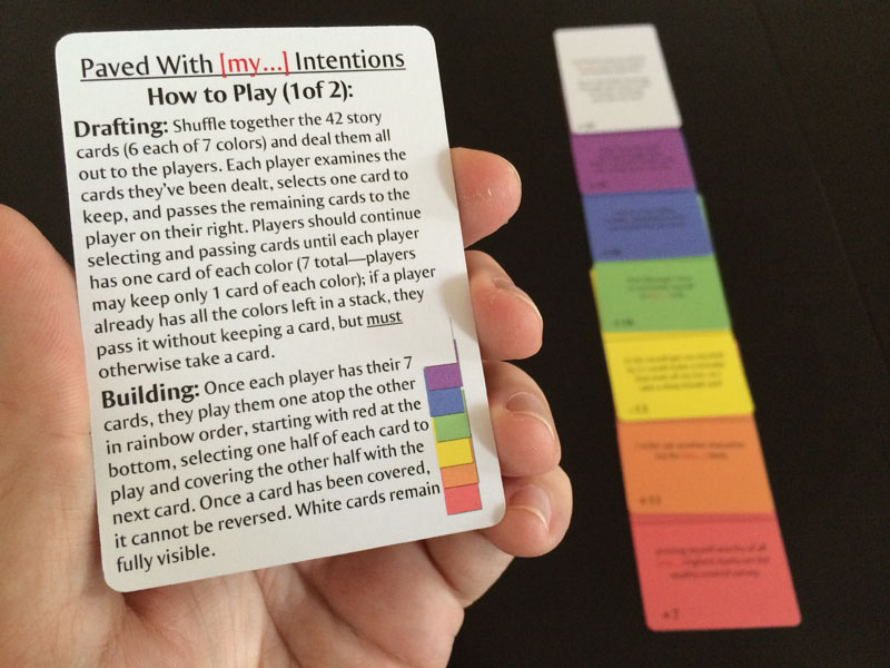 The first half of the instructions, with an example rainbow-layout in the background, from Paved With [my...] Intentions, a card game by Teel McClanahan III, from Modern Evil Press